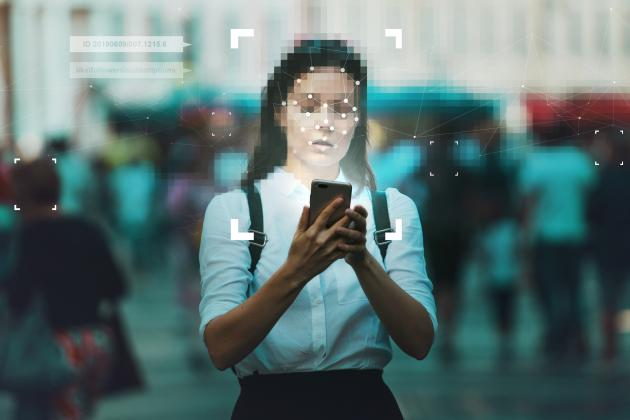 Person with face blurred out looks at phone