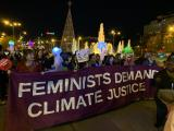 "Protesters carry sign saying ""feminists demand climate justice"""
