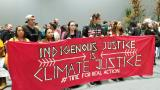 "Protesters carry a banner saying ""indigenous justice is climate justice"""